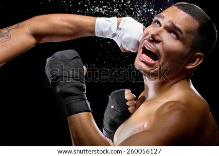 mma fighter or boxer losing and getting hit in the face - stock photo