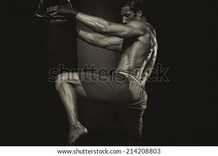 MMA Fighter Practicing Some Kicks With Punching Bag - A Man With A Tattoo In Red Boxing Gloves - Boxing On Black Background - The Concept Of A Healthy Lifestyle - The Idea For The Film About Boxing - stock photo