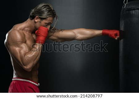 MMA Fighter Practicing With Boxing Bag - A Man With A Tattoo In Red Boxing Gloves - Boxing On Black Background - The Concept Of A Healthy Lifestyle - The Idea For The Film About Boxing - stock photo