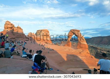 MOAB, UTAH/USA - August 12,2015; Some of the people standing in line to be photographed under the Delicate Arch and the other part is waiting for the sunset that would take a picture of a masterpiece - stock photo