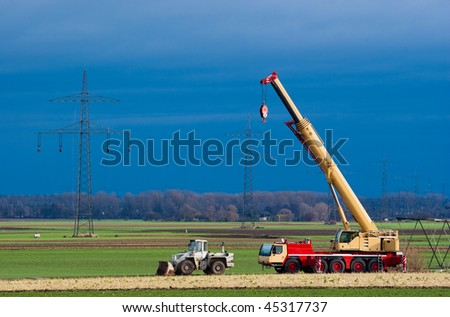 Mobil crane and transmission towers - stock photo