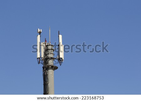 Mobile antenna in a tower against blue sky - stock photo