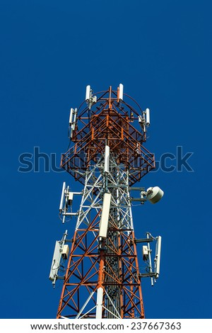 mobile antenna tower on blue sky - stock photo
