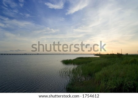 Mobile Bay in Alabama.  Sunset and baygrass. - stock photo