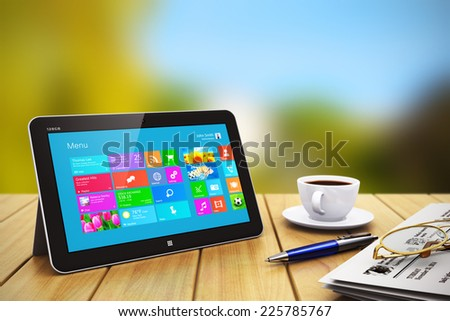 Mobile business internet communication and wireless office computer web work concept: modern tablet PC with touchscreen interface, newspaper, cup of coffee, pen and eyeglasses on wooden table outdoors - stock photo