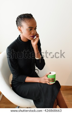 Mobile business woman in the office talking on her cell phone while holding disposable cup - stock photo