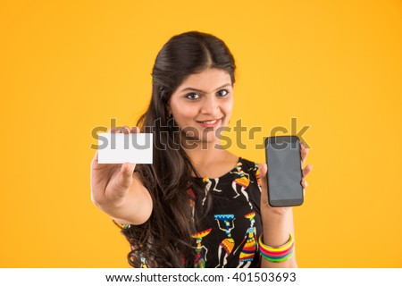 mobile commerce - smiling young indian girl making a banking transaction on cell phone with copy space credit card or blank white paper for modern convenience, isolated over yellow background - stock photo