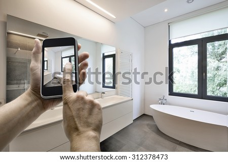 Mobile device with man hands taking picture in  tiled bathroom with windows towards garden - stock photo