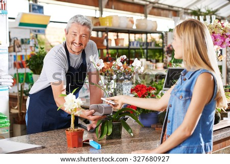 Mobile payment in garden center with salesman and customer - stock photo