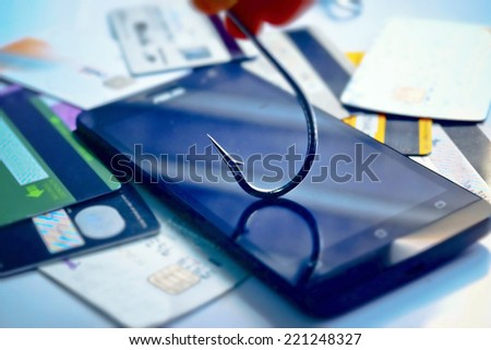 mobile phishing concept - a fish hook on a smart phone - stock photo
