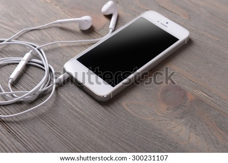 Mobile phone and earphones on wooden background - stock photo