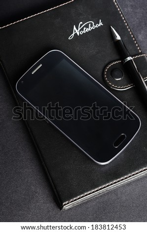 Mobile phone and notebook - stock photo
