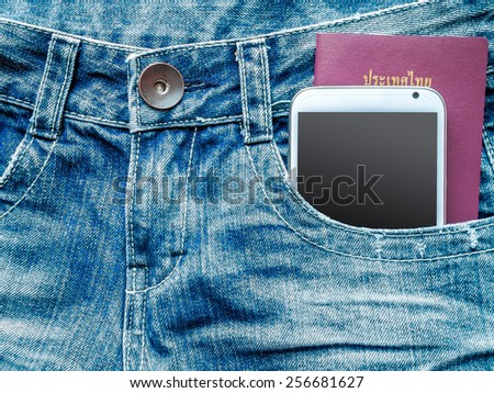 Mobile phone and  passport book in blue jeans pocket/ traveling concept - stock photo