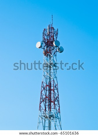 Mobile phone communication repeater antenna tower in blue sky - stock photo