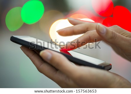 Mobile phone in a woman's hand, night, city ??of Light background, sms, message, e-mail  - stock photo