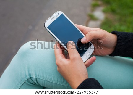 Mobile phone in a woman's hand on park background, message, sms, e-mail - stock photo