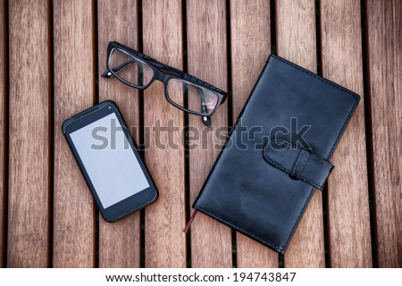 Mobile phone, notepad, glasses on wooden table. Business accessories concept. - stock photo