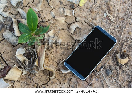 Mobile phone on the ground and small tree - stock photo