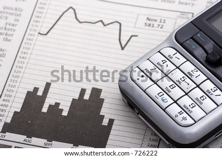 Mobile Phone Over Charts close up - stock photo