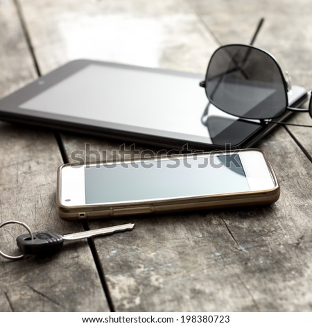 mobile phone, tablet and sunglasses on table, backlit - stock photo