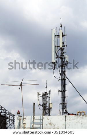 Mobile phone transmission pole on top of building - stock photo