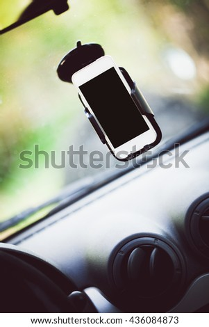 mobile phone with blank screen in car windshield holder - stock photo