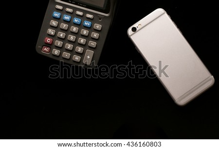 mobile phone with calculator use in business office black background - stock photo