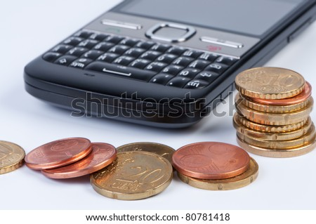 Mobile phone with coins closeup. Concept of money and cellular. - stock photo