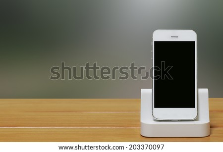 Mobile phone with dock station on blur background. - stock photo