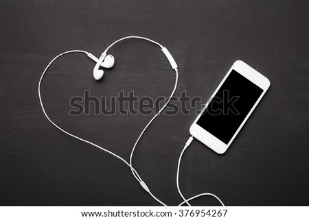 Mobile phone with headphones for music listening  - stock photo