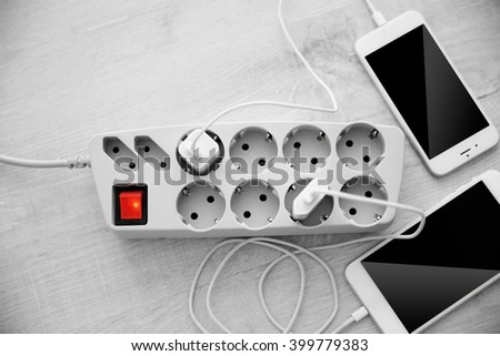 Mobile phones charging into power cord on wooden floor, top view - stock photo
