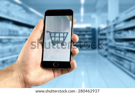 Mobile shopping concept. Hand holding mobile phone for internet shopping.Shopping cart symbol and supermarket in the background - stock photo