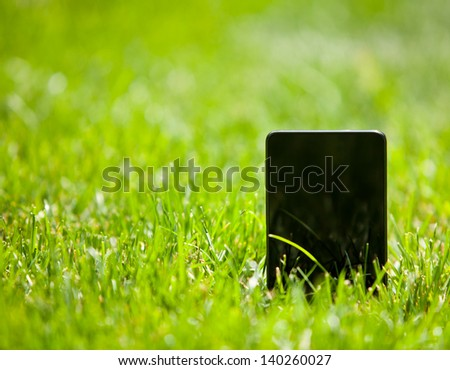 Mobile smart phone in green grass - stock photo