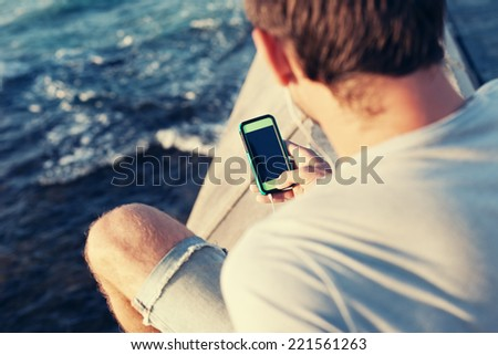mobile smartphone in man's hands near the sea - stock photo