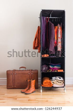 Mobile wardrobe with orange and purple clothing, and leather suitcase. - stock photo