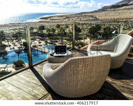 Mobile working on an southern island on a sunny terrace with view on palm trees and the blue sea. - stock photo