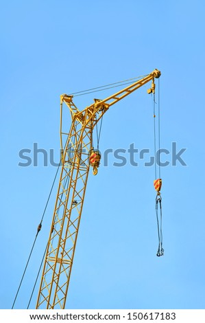 Mobile yellow construction tower crane against blue sky - stock photo