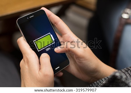 mobility and energy concept: girl using a digital generated phone with full battery on the screen. All screen graphics are made up. - stock photo