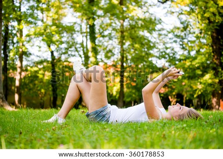 Mobility - teen girl lying on grass and working with smartphone - stock photo
