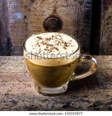 Mocha coffee in  Glass cup with foam cream topped with sprinkled chocolate on Old vintage dark wooden background, closeup - stock photo