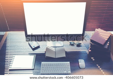 Mock up of home desktop with pc computer and digital tablet with blank copy space screen for your promotional content, keyboard with mouse, sunglasses, little notepad,books, modern hipster work space  - stock photo