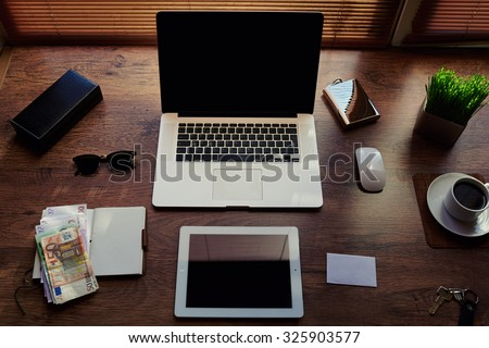 Mock up of successful person desktop with luxury accessories and distance work tools, portable laptop computer, digital tablet with blank copy space screen, money bills, notepad and cup of coffee - stock photo