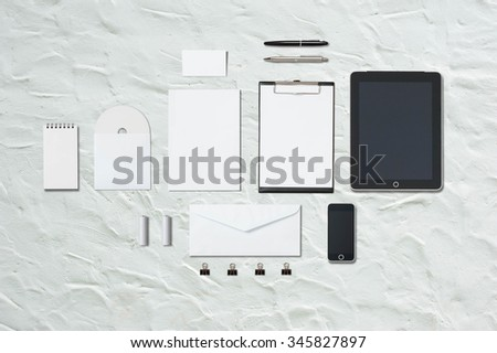 Mock up template of office equipment and stationary on white cement floor - stock photo