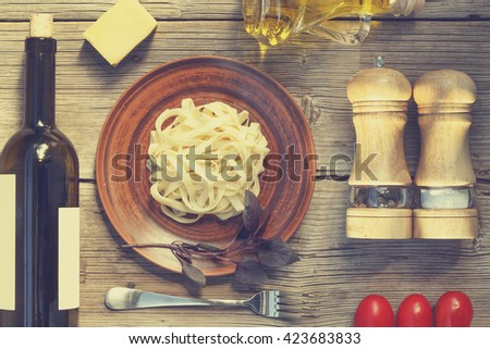 Mock Up. Wine. Pasta. Cherry tomatoes. Top view. Closeup. Spices. Italian food ingredients on wooden background. - stock photo