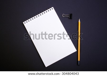 Mockup. Notebook drawing with a pencil on a black background. - stock photo