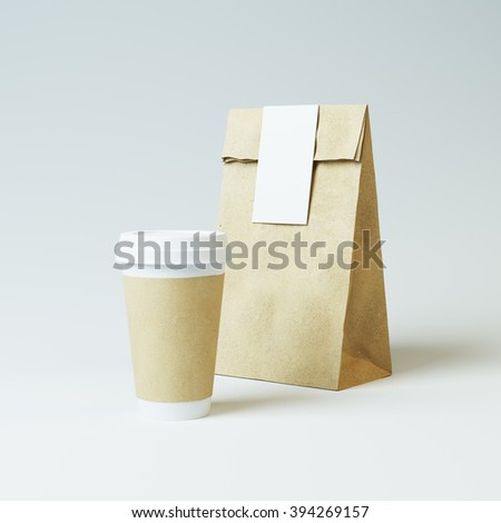 Mockup of craft paper bag and cup on light background - stock photo