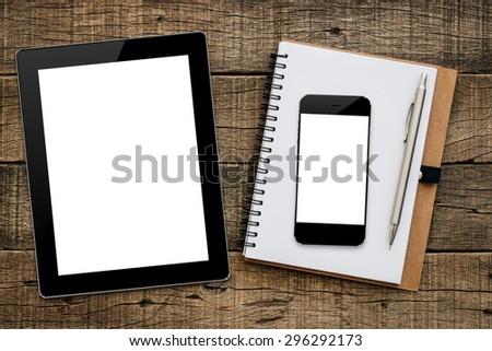 mockup tablet similar to ipad and phon on wood background - stock photo