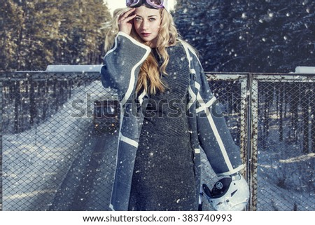 Model beautiful woman in fashionable clothes and accessories for skiing on the snowy bridge in winter - stock photo
