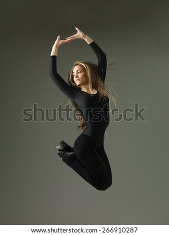 model dancer jumping and posing against grey studio background - stock photo