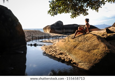 Model enjoying the sunset of the tropical island at Ilha Grande, Rio do Janeiro, Brazil. South America. - stock photo